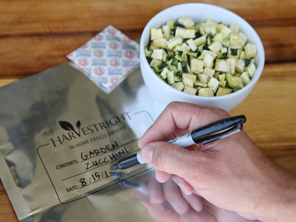 a hand writing on a mylar bag, an oxygen absorber, and a bowl of freeze dried zucchini