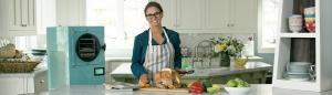 a woman in a kitchen preparing food next to an aqua freeze dryer