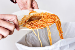 spaghetti being scraped into a garbage can