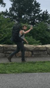 man wearing backpack, waving