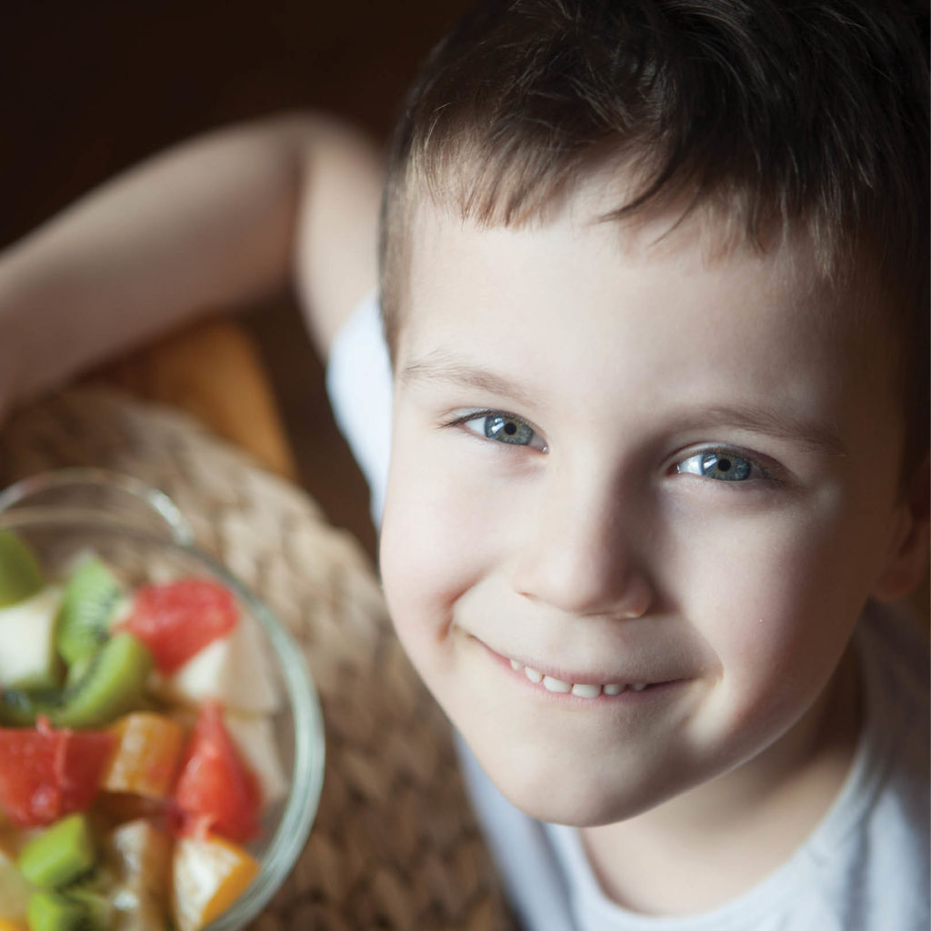 a smiling child with a bowl of fruit