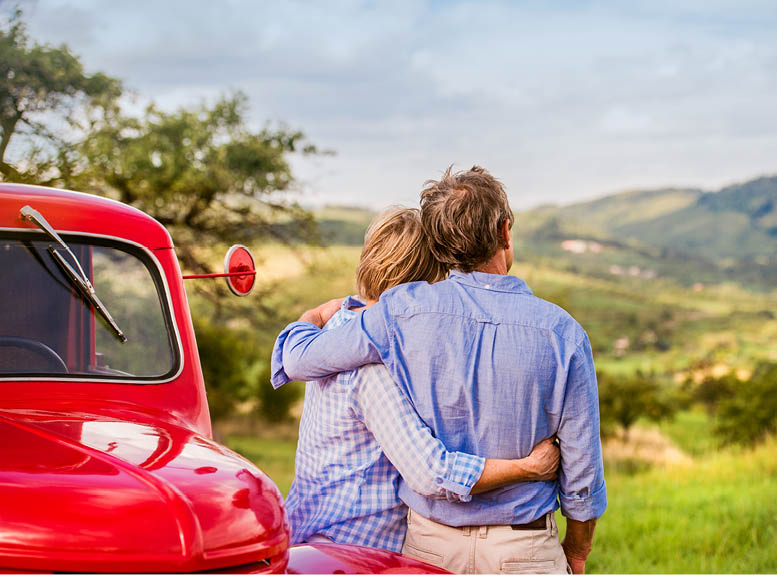 Man and woman embracing next to a red truck.