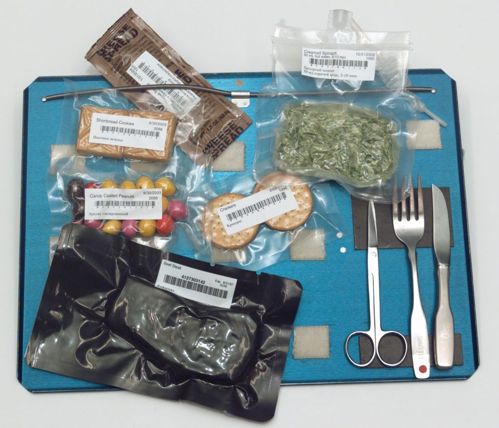 Packaged Astronaut food on a tray with eating utensils