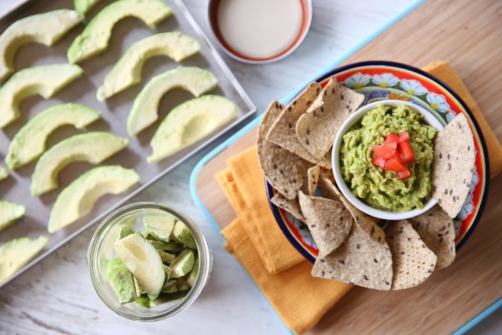 sliced freeze dried avocado next to chips and guacamole