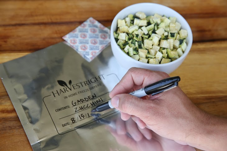 freeze dried zucchini in a bowl, a mylar bag, an oxygen absorber, and handing writing a description on the bag