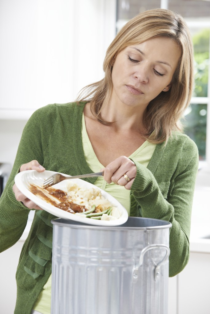 a woman scraping food off a tray into a trash can