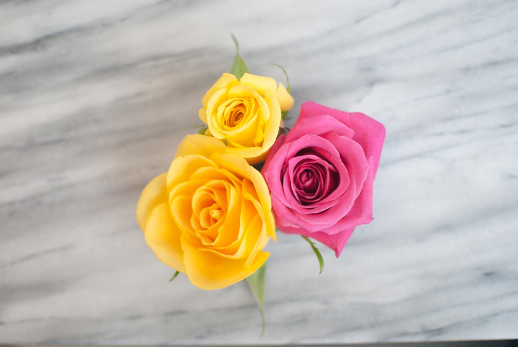 two yellow flowers and one pink flower