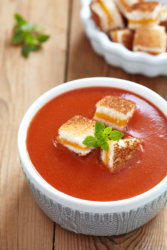 a bowl of tomato soup with Freeze Dried Grilled Cheese Croutons in it