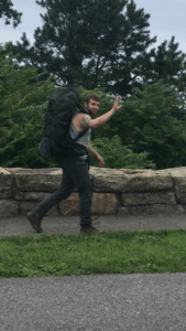 man wearing backpack, waving