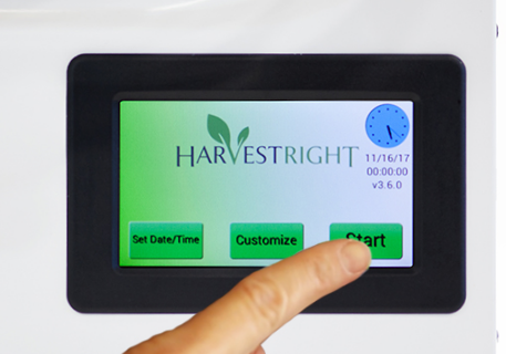 a close up of the Harvest Right control screen with a finger on the start button