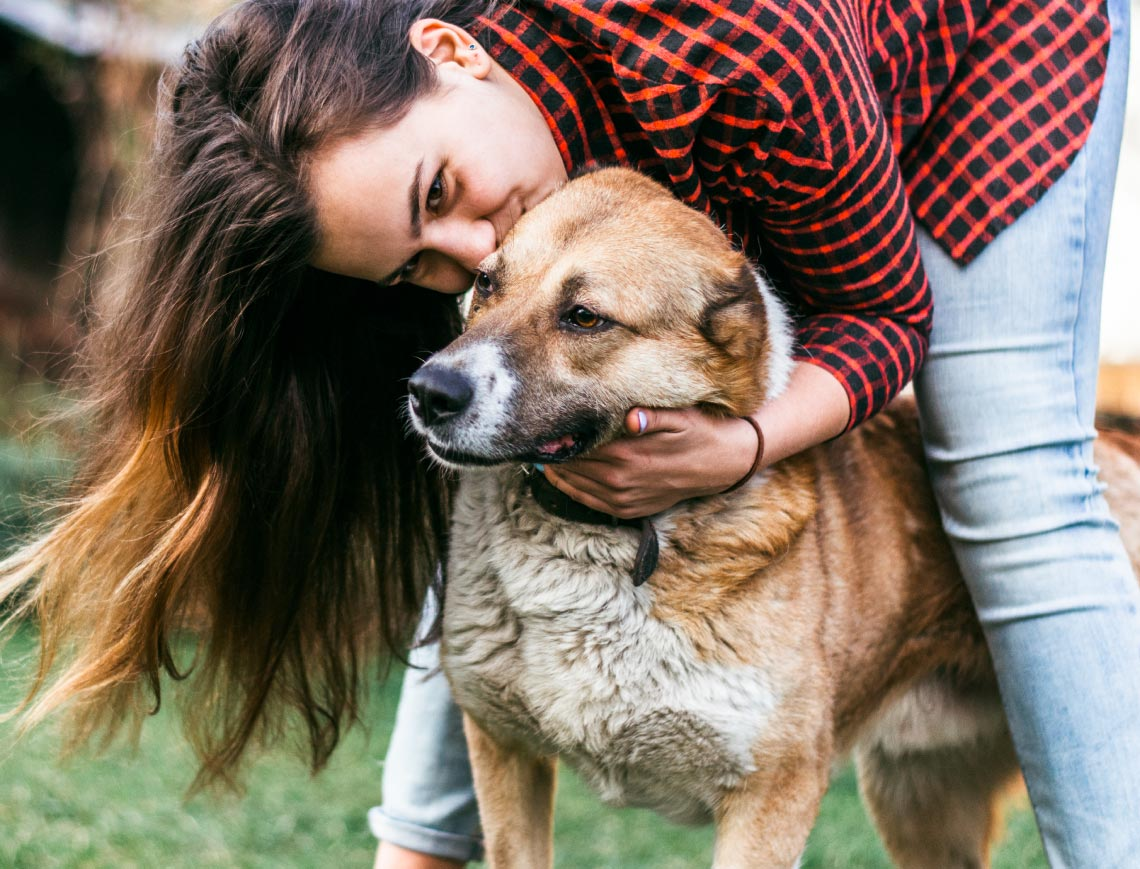 a woman hugging a tan dog