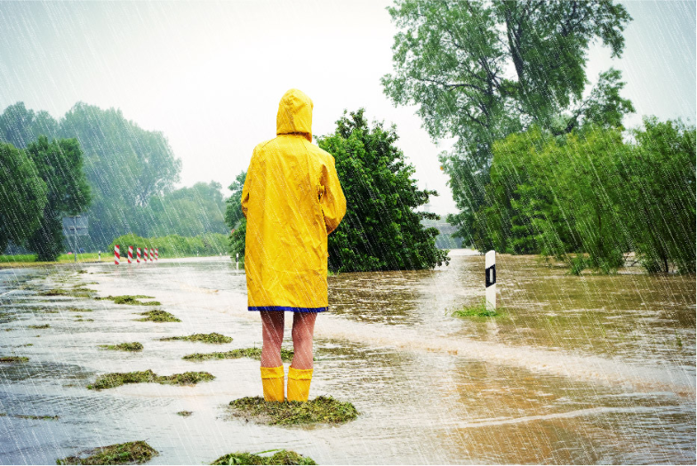 Person in yellow rain coat and boots standing in a flooded area
