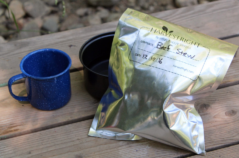 A camping mug and a bag of freeze dried food in a mylar bag on a wooden table