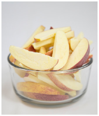Freeze dried apple slices in a clear glass bowl