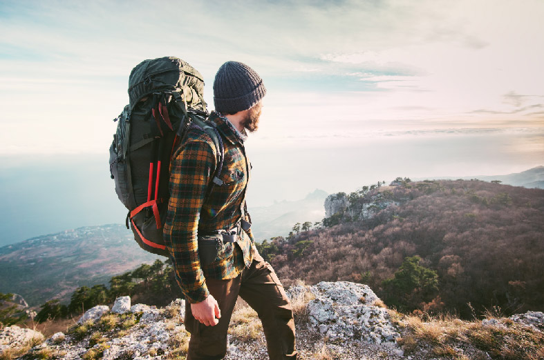 A man dressed in a beanie, a plaid long sleeve shirt, dark pants, and wearing a large hiking backpack, standing on a mountain.