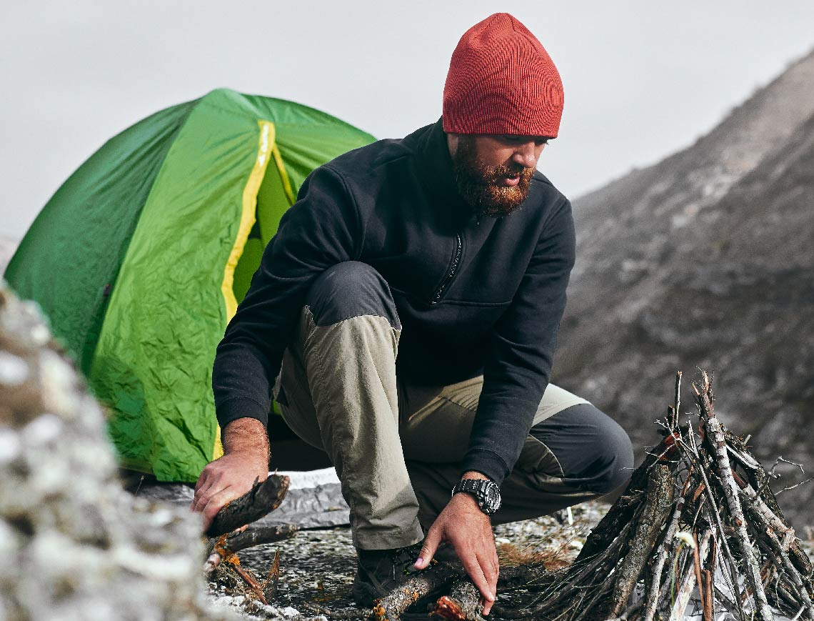 A bearded man dressed in camping wear, preparing a fire by a green tent.