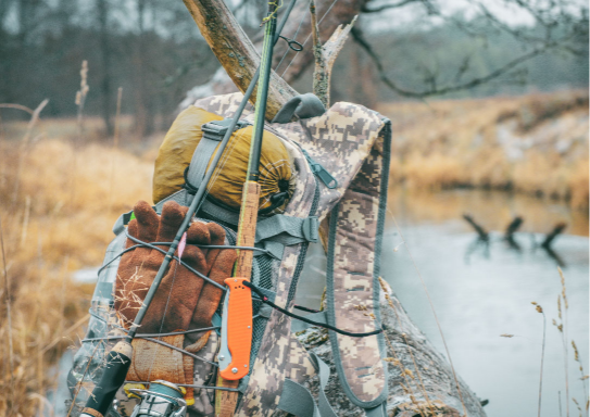 A camo backpack with fishing and camping gear.