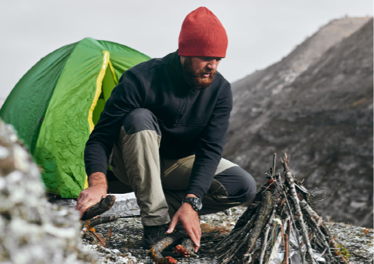 A man dressed in camping wear, preparing a fire by a green tent.