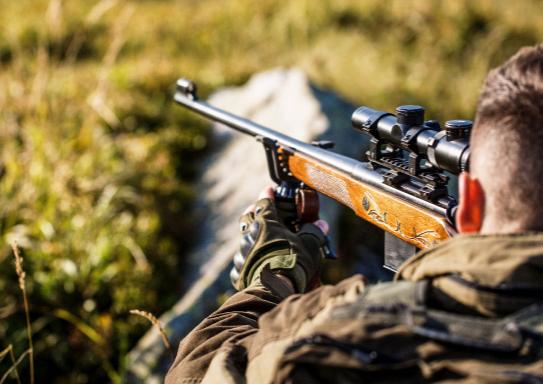 A man aiming a hunting rifle