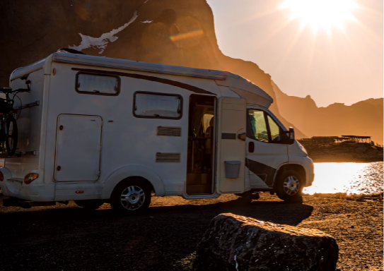 Rv parked by water at sunset