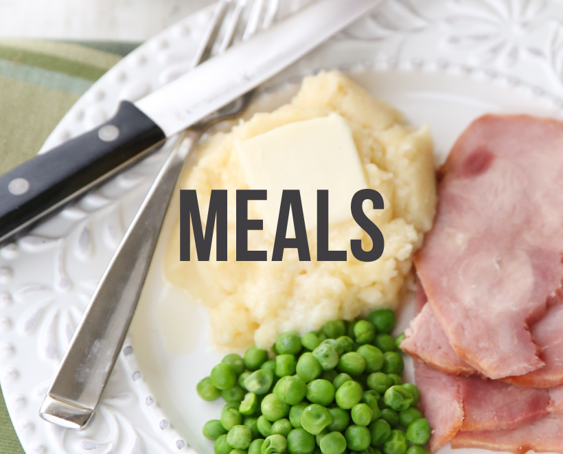 Meals. A plate of mashed potatoes and butter, ham, and peas